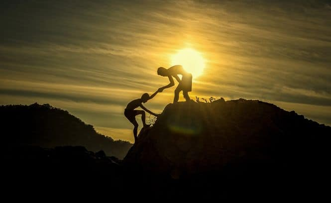 A silhouette of one person reaching his hand out to help another person up a mountain with the sun behind them.