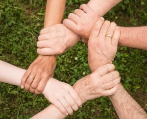 A downward shot of multiple hands grasping the wrist of the person to their right creating a circle of hands holding wrists.