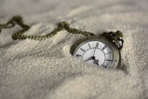 Pocket watch sinking in the sand