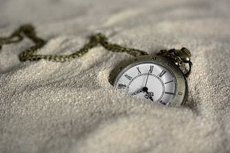 Pocket watch sinking in the sand.