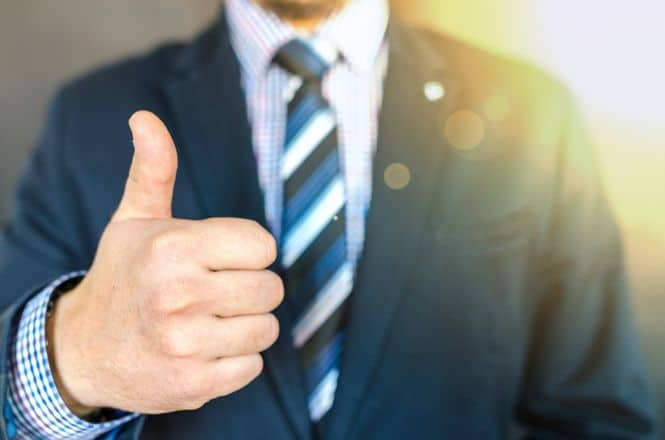 Man in a suit giving a thumbs up.