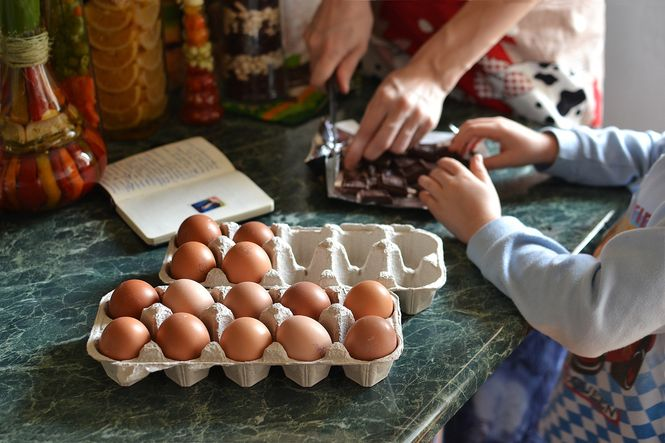 Close up photo of a family cooking together with eggs on the counter.