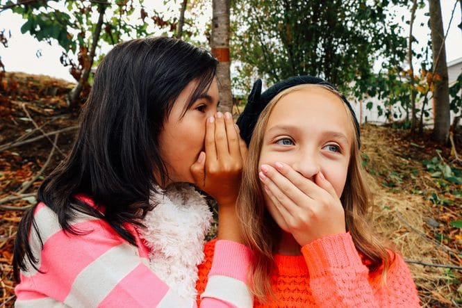 One girl whispering in another girl's ear.