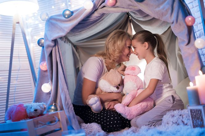 A mom and her daughter telling stories in a blanket fort.