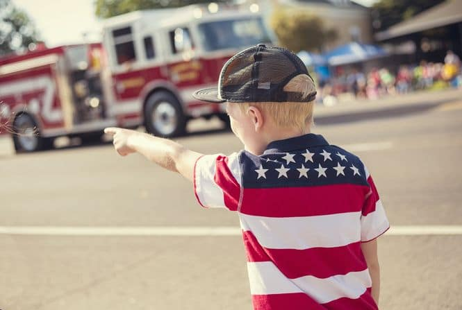 Young boy in a patriotic shirt at a parade pointing at a fire truck.