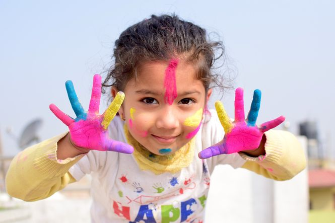 Young girl showing hands covered with colorful paint.