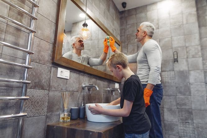 An image of a father showing his young son how to properly clean the bathroom.