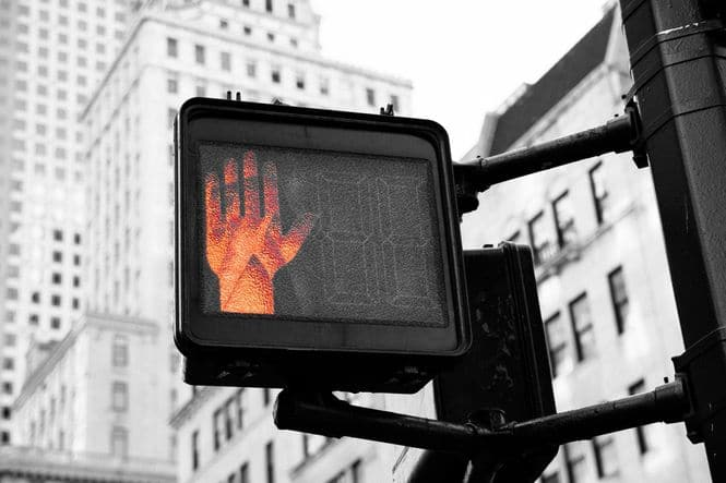 Crosswalk hand signal with red hand light for stop to symbolize not spending more money.