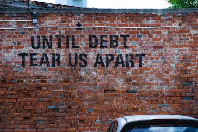 Brick wall with the words UNTIL DEBT TEAR US APART painted on the wall in all capital letters.
