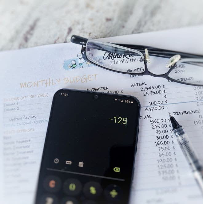 A monthly budget worksheet with a pen, calculate, and a pair of glasses in the image.