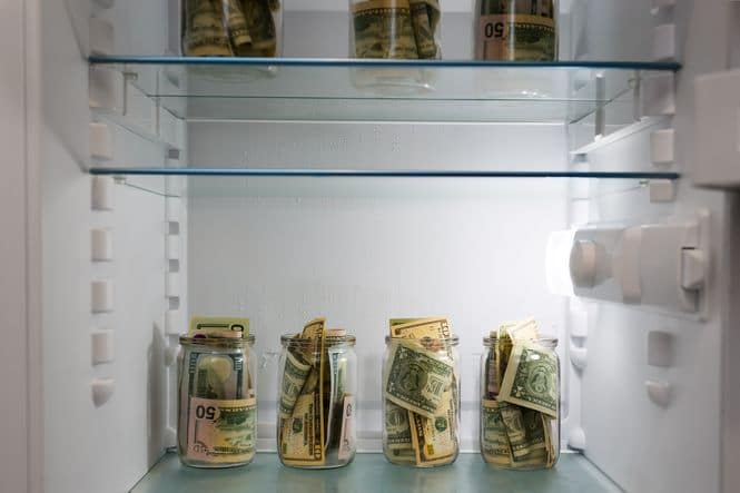 Dollars in a glass jar in the refrigerator.