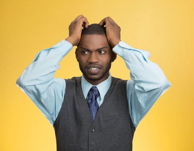 Closeup portrait, young, stressed, unhappy executive man with hands on temples, head about to explode, almost having nuclear meltdown, isolated yellow color background.
