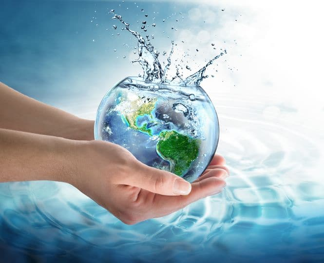A pair of hands holding a glass full of water with planet earth inside the bowl and water splashing out the top of the bowl on a ocean surface background.
