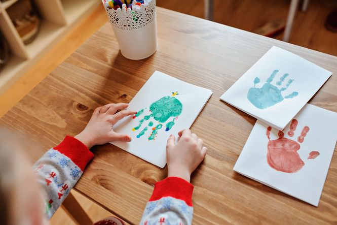 Child making handmade Christmas cards using handprints and paint.