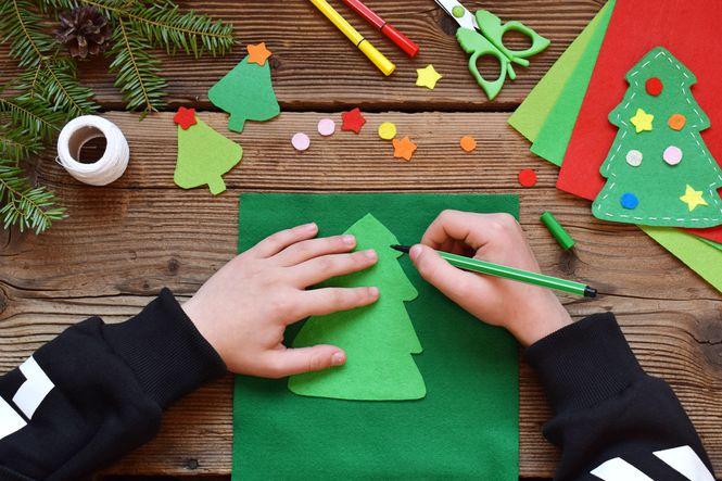 Child making handmade Christmas ornament for charitable family Christmas traditions.