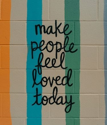 Make people feel loved today painted on masonry wall.