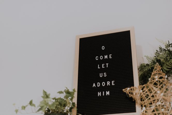 """""""O COME LET US ADORE HIM"""" spelled out on a black letter board with white letters."""