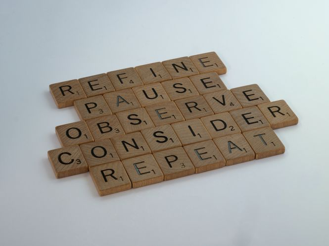 Scrabble blocks on a table spelling out refine, pause, observe, consider, and repeat to help build effective communication with your spouse.