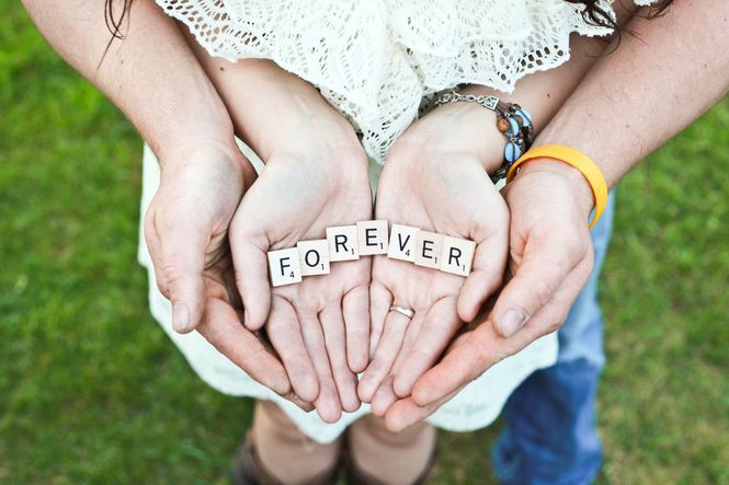 A young couple holding Scrabble letters in their hands that spell the word forever.