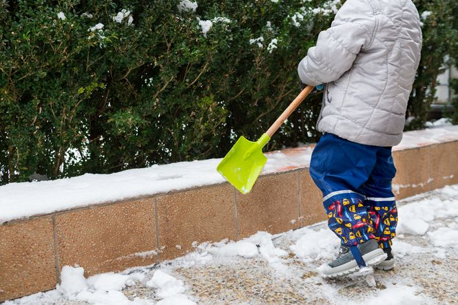Young child from the wait down helping to shovel snow.
