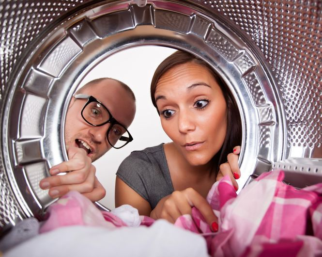 Man and woman looking into a dryer.