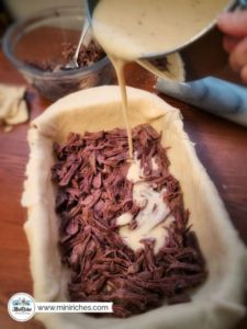 Pouring gravy on a layer of cooked shredded roast while making mouthwatering pot roast pie.