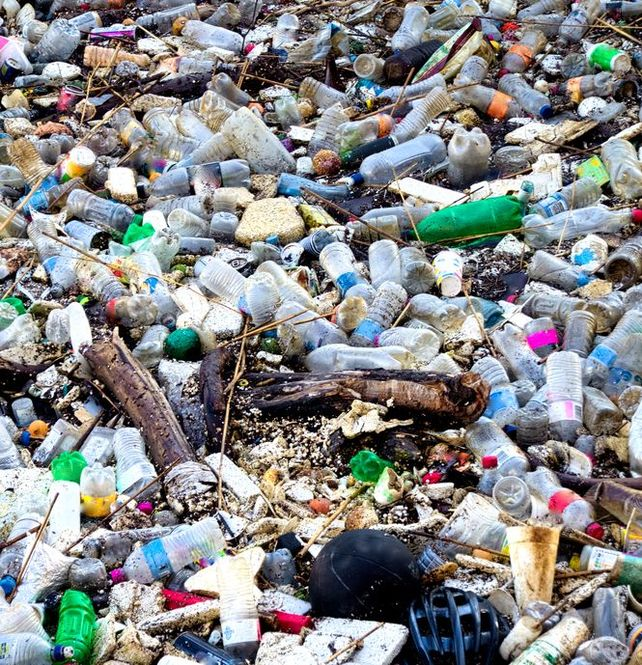 Save money as a stay at home mom by not using plastic bottles because they end up in a landfill like shown in this picture.