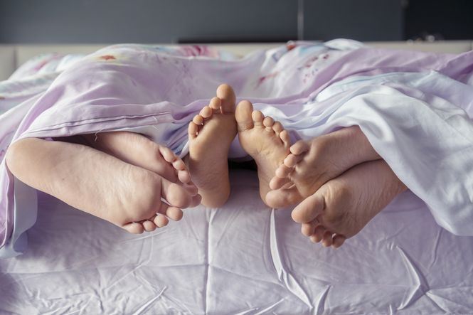 Kids feet in bed at an early bedtime to help find more time in the day.
