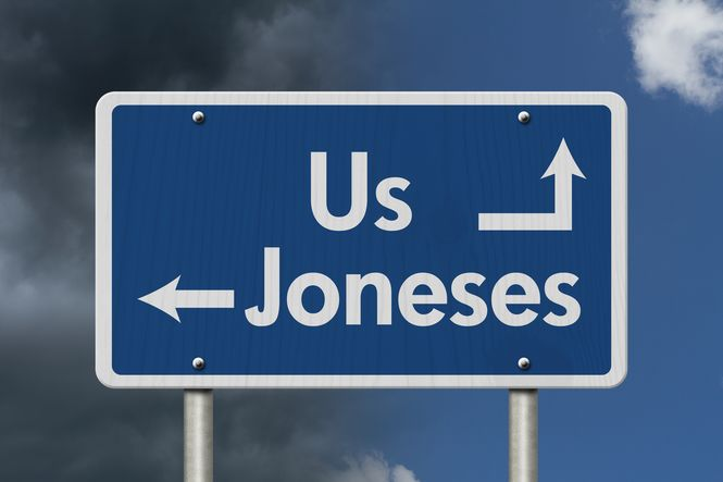 A sign showing us going one direction and the joneses going another to signify parental peer pressure.