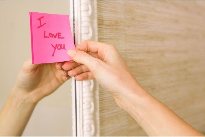"""Make a child feel special on their birthday by leaving messages. This is a picture of a hand leaving a sticky note on a mirror that says, """"I Love You."""""""
