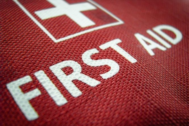 """Before leaving your child home alone, train them in first aid. This photo is a close up of a first aid bag with a white cross and the words, """"FIRST AID."""""""