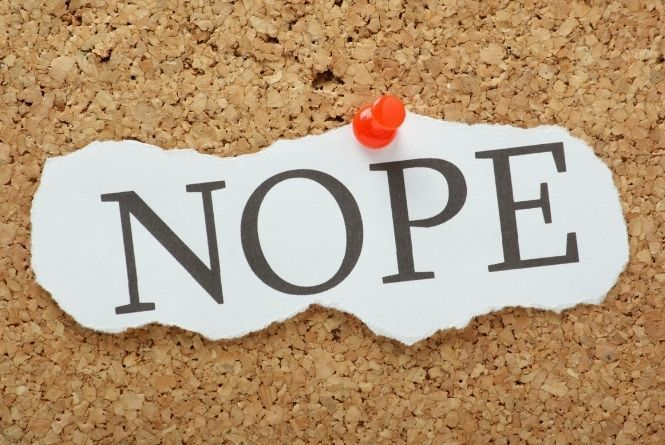 Pregnancy shaming affects mental health. This is a photo of the word NOPE on a piece of paper pinned to a corkboard.