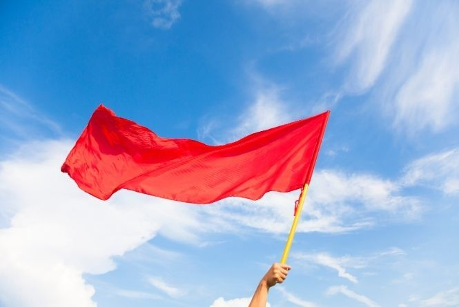Do you see any red flags when it comes to leaving your child at home alone? This is a picture of a hand waving a red flag against a blue sky with white clouds.
