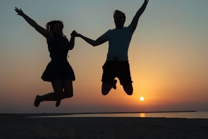 Stand tall through pregnancy shaming! This is a photo showing the silhouette of a man and a woman happily jumping in the air with the sunset behind them.