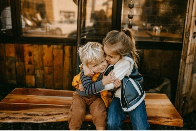 When and how to teach manners to kids can include hugging. This is a picture of a little boy and girl hugging each other.