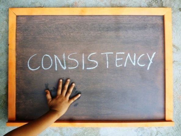 """Be consistent when young siblings fight. This is a picture of a hand on a chalkboard with the word """"CONSISTENCY"""" on the chalkboard."""
