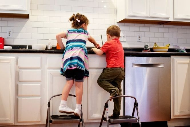 When young siblings fight, have them do chores together. This is a picture of a brother and sister standing on stools to wash the dishes together.