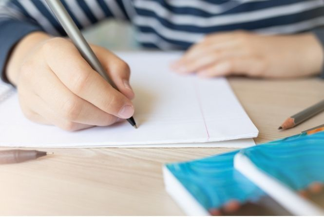 When young siblings fight, have them write letters of affirmation to each other. This is a picture of a hand writing on a piece of notebook paper.