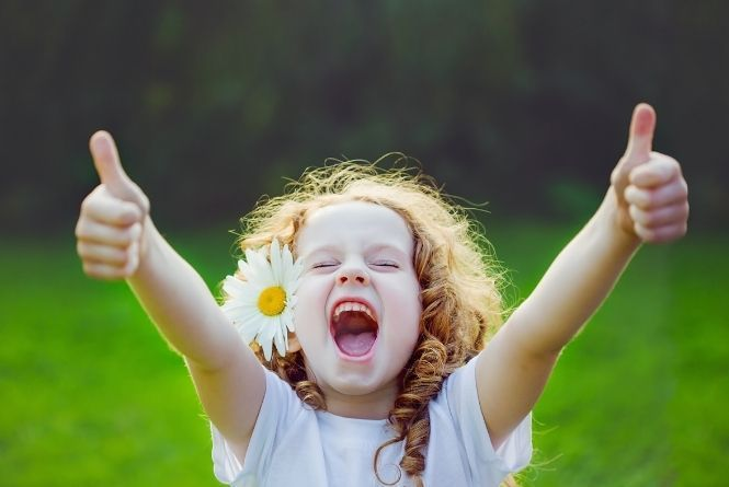 When young siblings fight, use natural consequences to help them remember. This is a picture of an excited little girl giving two thumbs up.