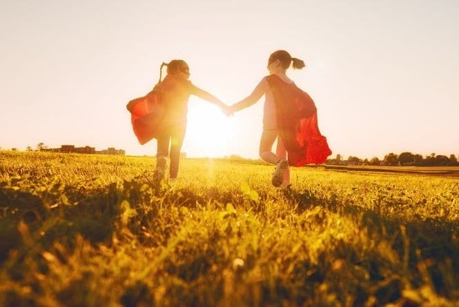 One of the benefits of having more than one child is being able to face fears together. This is a picture of two little girls wearing superhero costumes as they run through a grassy field toward the setting sun.