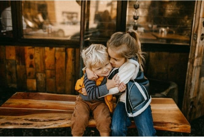 One of the benefits of having more than one child includes teaching unconditional love. This is a photo of a little boy and a little girl hugging each other.