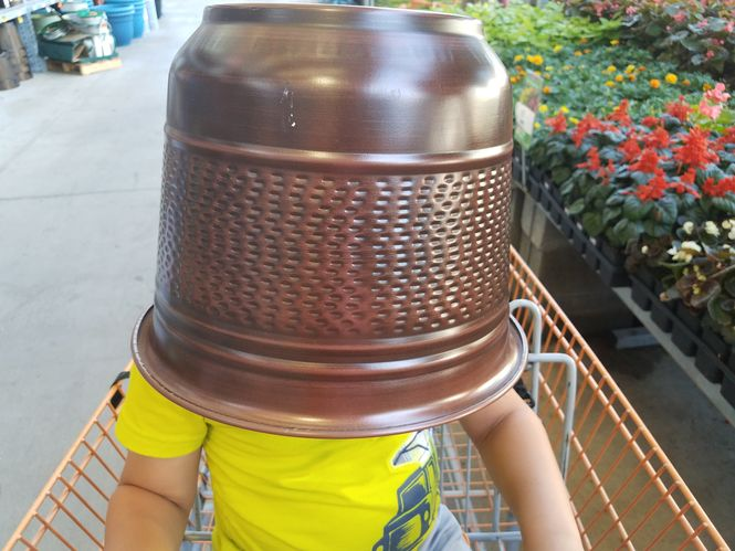 Manage your child's temper tantrum in public by being fun. This image shows a little child sitting in a shopping cart in the lawn and garden section with a flower pot on his head.