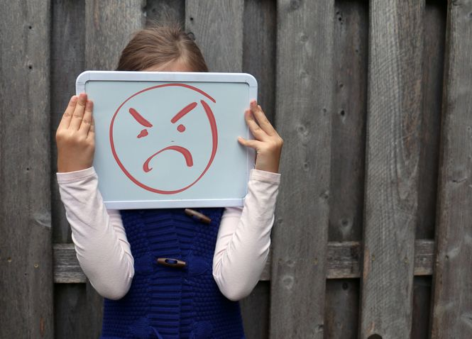What is a child's temper tantrum in public? This image shows a young child holding a whiteboard in front of their face. There is an angry face drawn on the whiteboard in red.