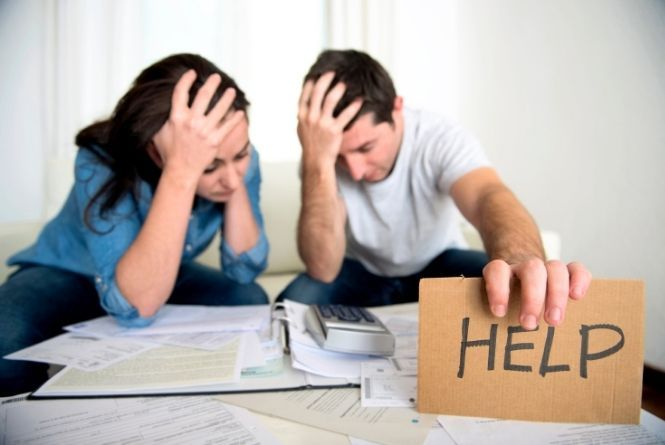 """Ask for financial help to help lower expensive medical bills. This is a image showing a distressed couple looking over bills and holding up a sign that says, """"HELP."""""""