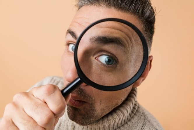You can lower expensive medical bills by looking them over before paying them. This is a picture of a man holding a magnifying glass up to his eye.
