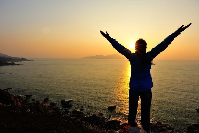 Growing your family does not need to be difficult. This is a image showing a silhouette of a woman holding her arms up in hope with the ocean and sunset in the background.